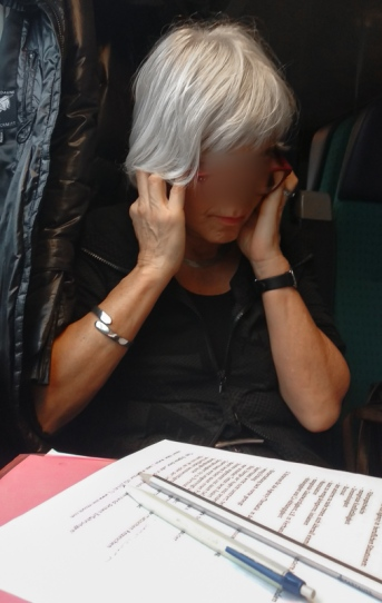 Gray haired woman reading on the train and shutting her ears with her fingers.