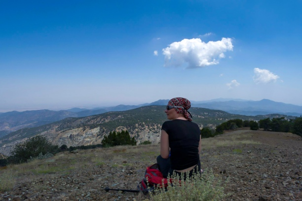 Woman hiker. Clear sky on top of a mountain with more mountains in the distance.