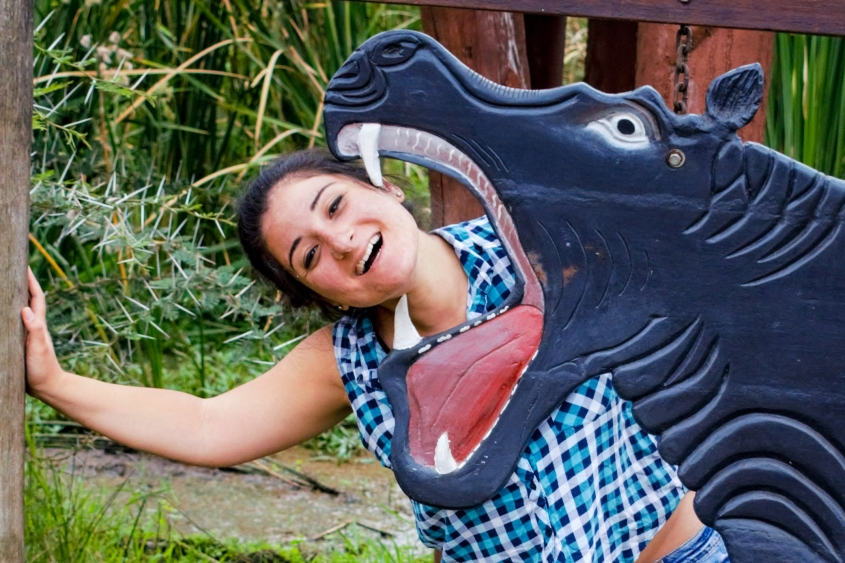 Fake wooden hippo taking a bite of neck of girl outdoors